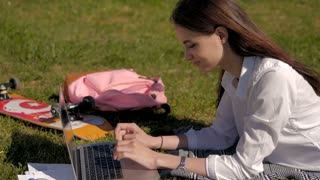 Side View of a Young Student Using Her Laptop While Lying On The Grass In a Park