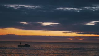 Silhouette of Fishermen with his Boat in Ocean