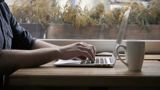 Silhouette of Happy Young Man Freelancer with Modern Laptop in Cafe taking Cup of Coffee