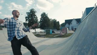 skateboarder in action on a ramp, doing stall trick, rock to fakie on skateboard