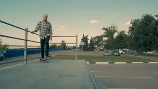 Skateboarder is dropping with his Skateboard a Ramp, rock to fakie