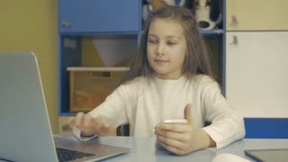 Smart Kids. Small Schoolgirl is Sitting at the Desk and using Laptop