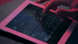 sound engineer's hand moving sliders on audio mixing board on tablet on concert