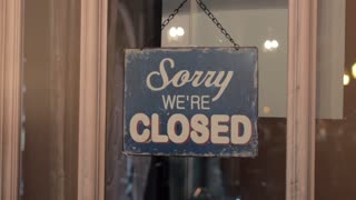 The closed and open sign on a glass door