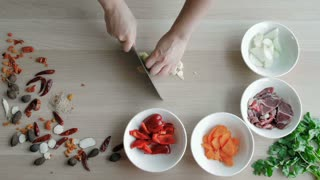Top View of Chefs Hands Chopping Ginger And Garlic On Wooden Board, Healthy Food Concept
