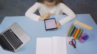 Top View of SchoolGirl Studying at the Library Doing after lessons Homework with tablet PC. Elementary school. Child reading