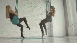 Two Pretty Girls- Aerialist Doing Acrobatic Tricks On Aerial Silks