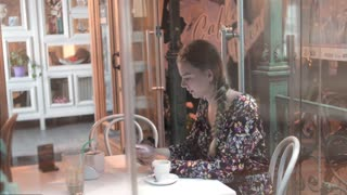 View through coffee house window with city reflection of woman is using mobile phone, . Young student with smart phone is resting after university