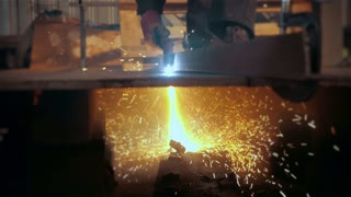 Welder in factory welding metal in modern stock workshop