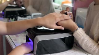 woman in a nail salon receiving a manicure by a beautician with nail file. Woman getting nail manicure. Beautician file nails to a customer. Blurred background