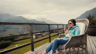 Woman tourist dressed in stylish clothes shoots video of beautiful mountain landscape on cell telephone, hipster girl taking photo with mobile phone camera while sitting near mountains in cool spring