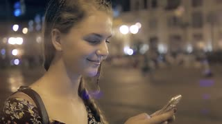 Woman tourist is searching way in navigation via cell telephone, while is standing on the street in night. Student Girl is searching information in network via smart phone, during walk in an