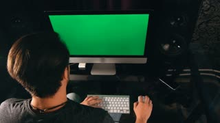 Working late. Confident young man working on his laptop PC with chroma key green screen while sitting at his working place at night time. Handsome freelancer workspace. Creative manager at work