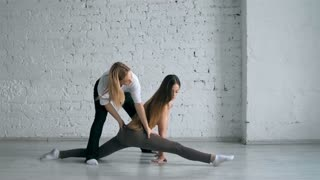Yoga Trainer Helps Female Student To Stretch Legs And Do The Splits
