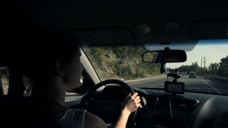 Young Beautiful Black-Haired Woman Driving Car - Rear View