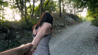 Young Beautiful Brunette Woman Leading By Hand Her Lover On Mountain Road, Follow Me Concept