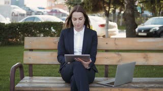 Young Beautiful Business Woman Using Tablet PC Sitting On Bench Outdoors