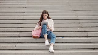 Young beautiful stylish girl sits on steps and holding hands in the tablet. Girl student communicates in social networks with friends
