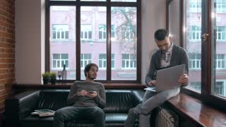 Young freelancers working at the modern office. Businessmans with devices, laptop and tablet in coworking