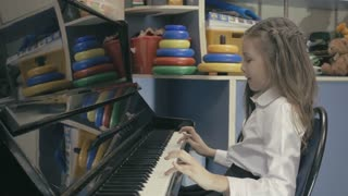 Young Girl Playing Piano in School Class