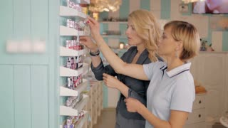Young girls choosing new nail polish tone at cosmetic shop, best friends in supermarket