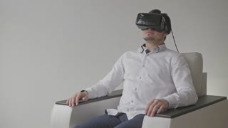 Young Handsome Caucasian Man on Sofa Wearing VR Headset Glasses