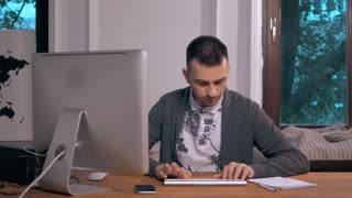 Young hispanic attractive hipster 30s businessman working busy at modern home office with computer laptop dressing casual in creative freelancer business success concept