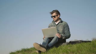 Young Man In Sunglasses Using Laptop Outdoors Sitting On The Grass In Park