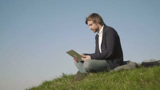Young Man Talking On Skype Using a Laptop While Sitting On The Grass In The Park