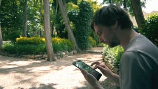 Young Man tourist Sitting In Park And Holding Digital Tablet