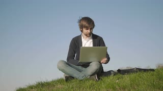 Young Man Using Laptop Outdoors Sitting On The Grass In Park
