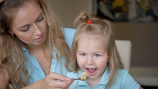Young mother feeds her young child from a spoon. Oatmeel breakfast with mother and daughter