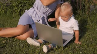 Young Mother With Her Little Cute Son Sitting On Grass And Using Laptop