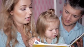 Young parents read the book to children at home. Mother Father and Daughter reading