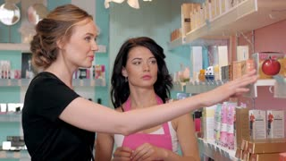 Young smiling woman choosing new cream tone at cosmetic shop
