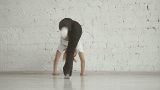 Young Sportive Girl Show Acrobatic Tricks Against The Wall