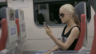 Young tired blonde woman using smartphone in subway train at metro