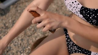 Young Woman Applyng Sun Protector Cream At Her Hand On The Beach