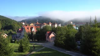 Scenery of Carpathian Houses With Roofs Under Fog
