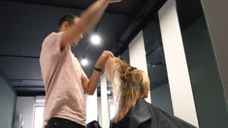 Stylist, Hairdresser is Making The Hairstyle For a Woman with Long Hairs, Combing the Wet Hairs before making a hairstyle