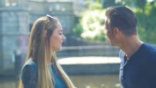 A couple talk on the riverside - They have small differences, but can easily find a compromise