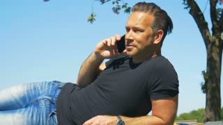 A handsome man enjoys a summer day and talks on the cellphone