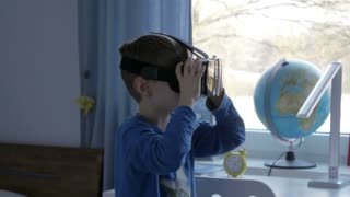 Boy in virtual reality glasses playing 360 degree game - 4k