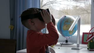 Boy in virtual reality glasses watching 360 degree video - 4k