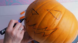 Family preparing for Halloween. Drawing a demon face on a pumpkin with a marker