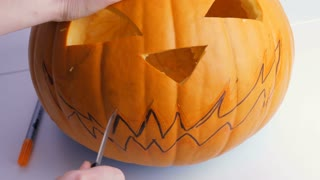 Family preparing for Halloween. Hands carve a jack o lantern from a pumpkin