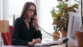 Female receptionist working on computer and talking on phone in call center
