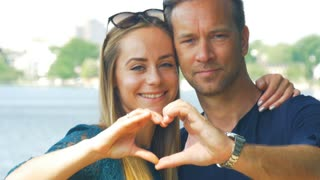 Handsome couple in love making heart shape with hands.