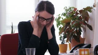 Sick at work - A young secretary taking a pill for a headache