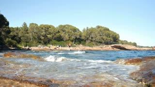 Tourists sun bathing on rocky beach lagoon - 4k